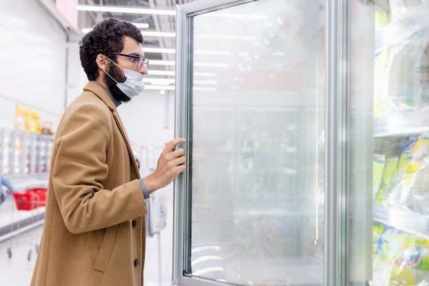 Jonge man in de supermarkt in de afdeling met diepvriesproducten. een brunette in een medisch masker tijdens de pandemie van het coronavirus.