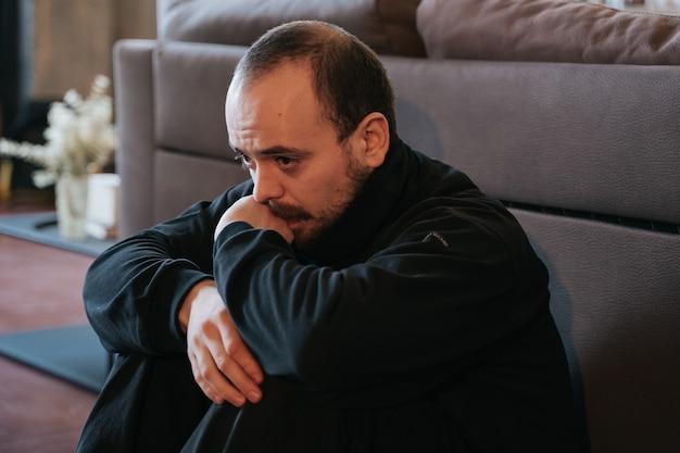 Jonge man in depressie, bezorgd en verdrietig, bebaard. alleen zitten