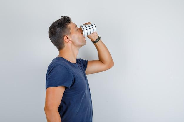 Jonge man in donkerblauw t-shirt kopje koffie drinken.