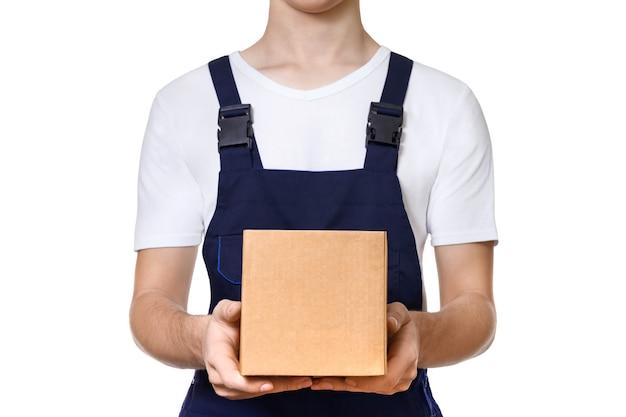 Jonge man in donkerblauwe overalls en een wit t-shirt met kartonnen doos voor hem, geïsoleerd op een witte muur. leveringsconcept.