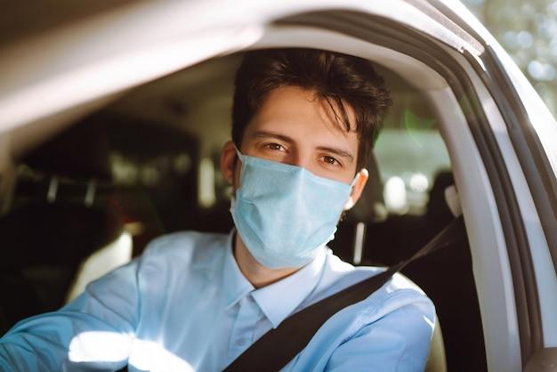 Jonge man in een beschermend masker in de auto zitten