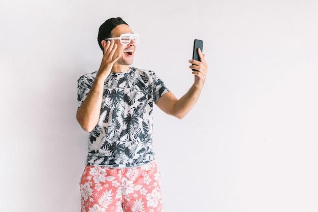 Jonge man in een bloemenshirt, pet en bril in de zomer die een selfie en een videoconferentie neemt met zijn smartphone en een cocktail drinkt met een rietje, bij daglicht op een witte muur