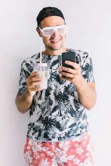 Jonge man in een bloemenshirt, pet en bril in de zomer kijkend naar zijn smartphone en een cocktail drinkend met een rietje, bij daglicht op een witte muur