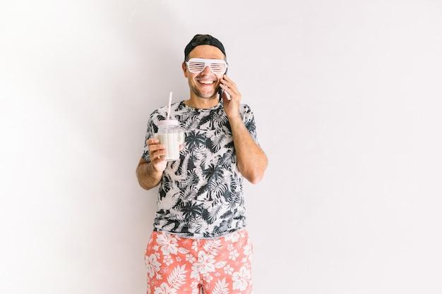 Jonge man in een bloemenshirt, pet en bril in de zomer praten op zijn smartphone en een cocktail drinken met een rietje, bij daglicht op een witte muur