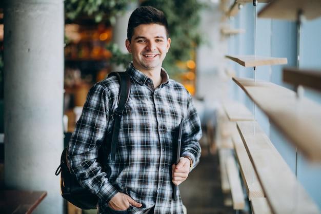 Jonge man in een café bij het raam staan en praten over de telefoon