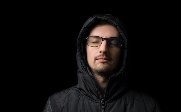 Jonge man in een capuchon en bril op een zwart