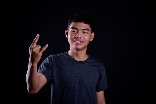 Jonge man in een donker t-shirt een rocker gebaar maken