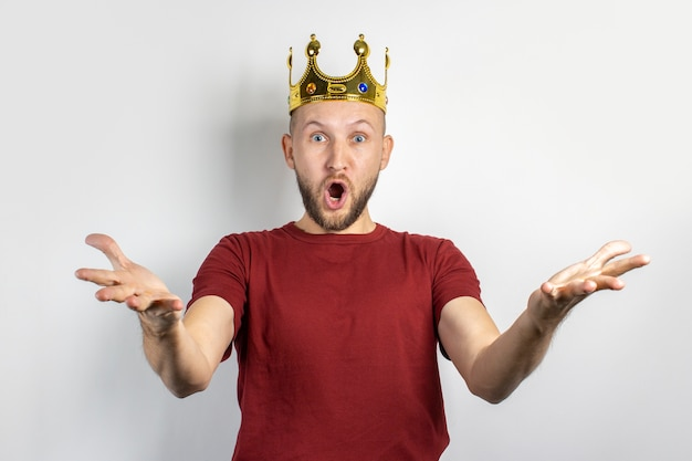 Jonge man in een gouden kroon met een verbaasd gezicht op een lichte achtergrond. concept koning, geluk, winst, rijk, droom, doel, ambitie, weddenschap. banner.