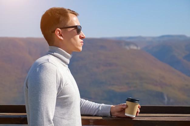Jonge man in een grijze coltrui en zonnebril drinkt een drankje uit een plastic glas op een achtergrond van bergen op een heldere dag, zonlicht