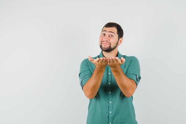 Jonge man in een groen shirt die zijn handen combineert met een vragende manier, vooraanzicht.