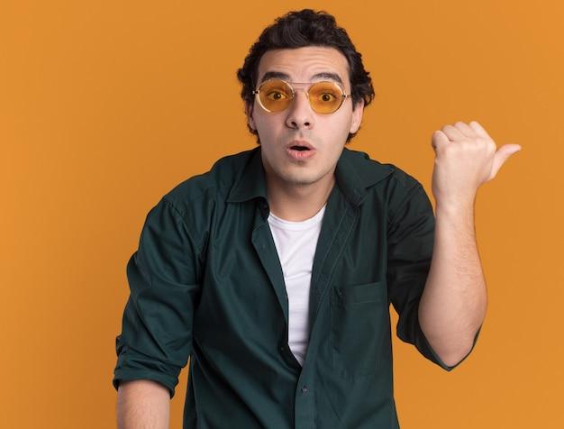 Jonge man in een groen shirt met bril kijken naar voorkant verward wijzend met duim naar de zijkant staande over oranje muur