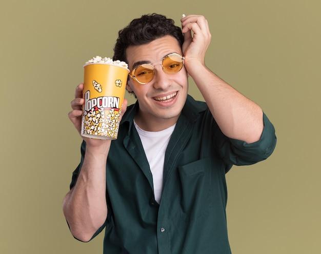 Jonge man in een groen shirt met bril met emmer met popcorn kijken naar voorzijde blij en vrolijk lachend staande over groene muur