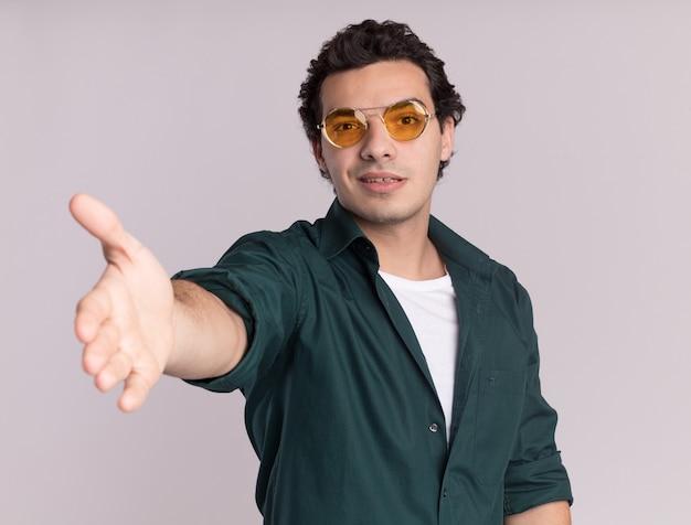 Jonge man in een groen shirt met bril op zoek naar de voorkant met handgroet glimlachend vriendelijk staande over witte muur
