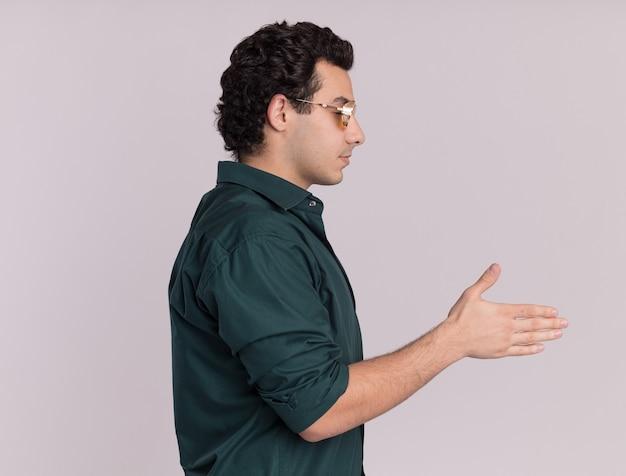 Jonge man in een groen shirt met een bril die zich zijwaarts bevindt en handgroet over witte muur aanbiedt