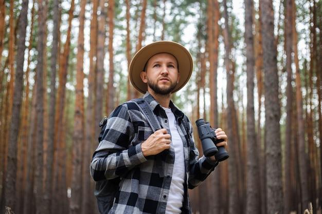 Jonge man in een hoed met een rugzak en een verrekijker in een dennenbos. wandeling in de bergen of in het bos.