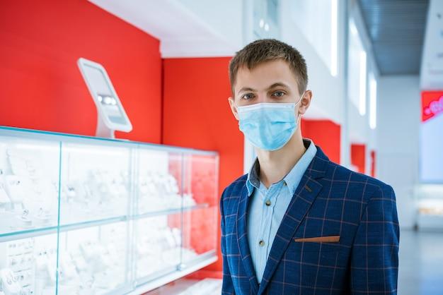 Jonge man in een juwelier in een jasje en een medisch masker kiest sieraden