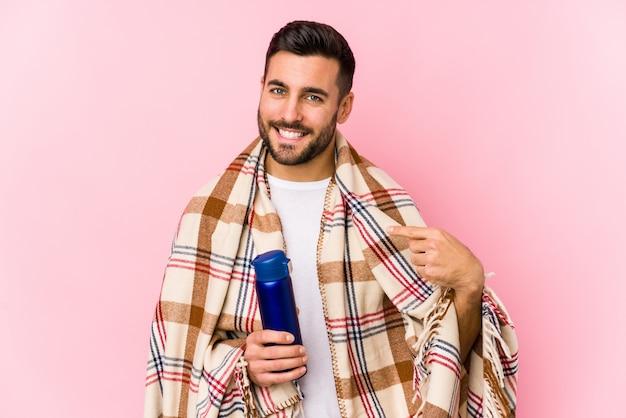 Jonge man in een kamperende persoon die met de hand wijst naar een lege ruimte van een shirt, trots en zelfverzekerd