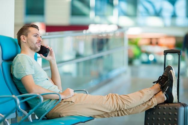 Jonge man in een lounge op de luchthaven te wachten voor vliegtoestellen.