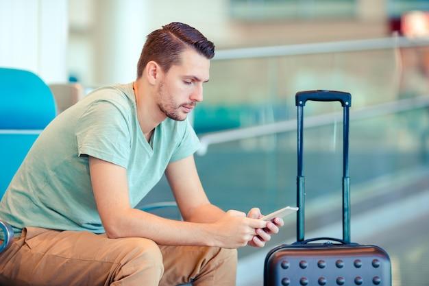 Jonge man in een luchthavenlounge die op vluchtvliegtuigen wacht.