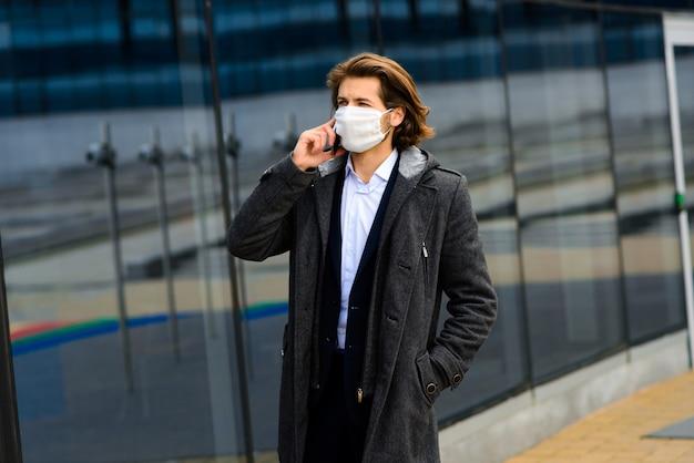Jonge man in een medisch masker buiten, geen geld, crisis, armoede, ontbering. quarantaine, coronavirus, isolatie.