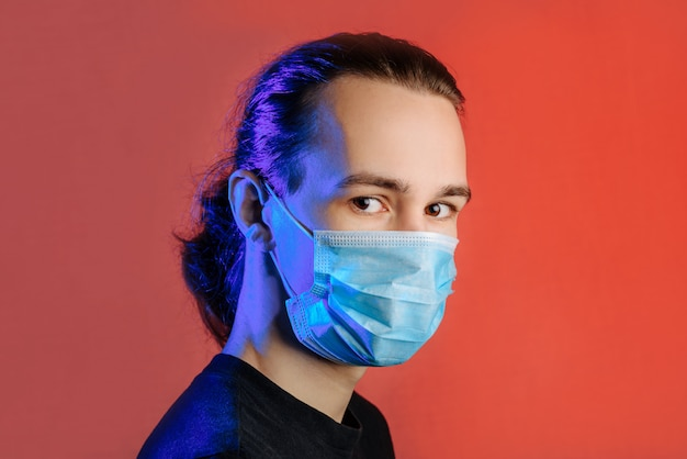 Jonge man in een medisch masker op een rode muur close-up met een kopie ruimte.