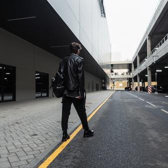 Jonge man in een modieuze leren jas in vintage jeans in stijlvolle laarzen met een trendy zwarte rugzak loopt in de buurt van de weg in de stad. moderne man in kleding in amerikaanse stijl. uitzicht vanaf de achterkant.