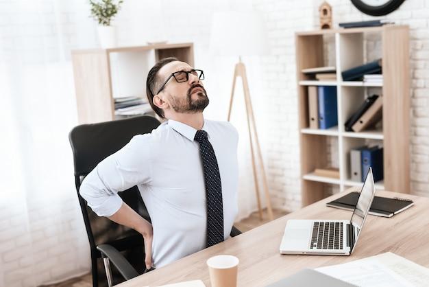 Jonge man in een pak en een bril met zijn rug