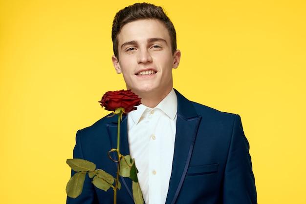 Jonge man in een pak met een roos in zijn handen