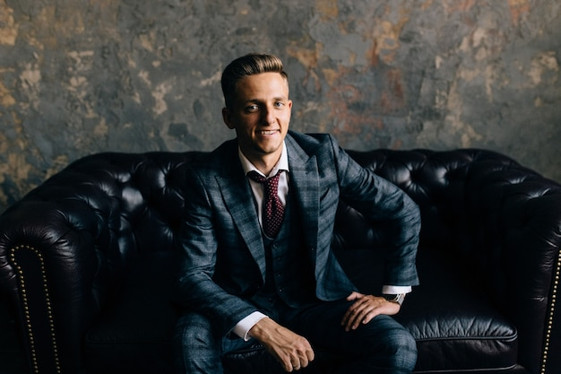 Jonge man in een pak zittend op een bank glimlachen