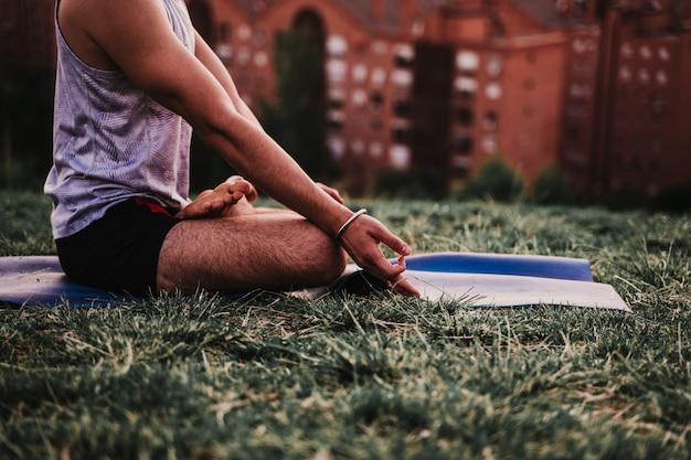 Jonge man in een park beoefenen van yoga sport
