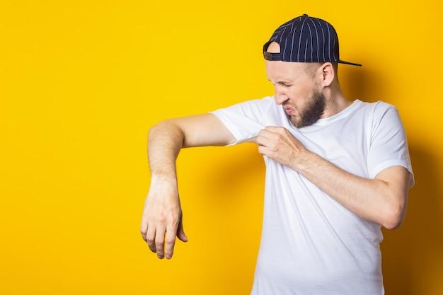 Jonge man in een pet en een t-shirt snuift zijn oksels op een gele achtergrond. zweetconcept, zweetvlekken.