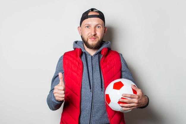 Jonge man in een pet, hoodie en vest houdt een voetbal vast en toont het gebaar dat alles in orde is