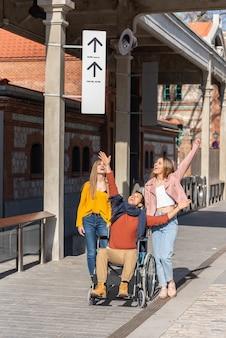 Jonge man in een rolstoel gooien een hoed met twee jonge meisjes