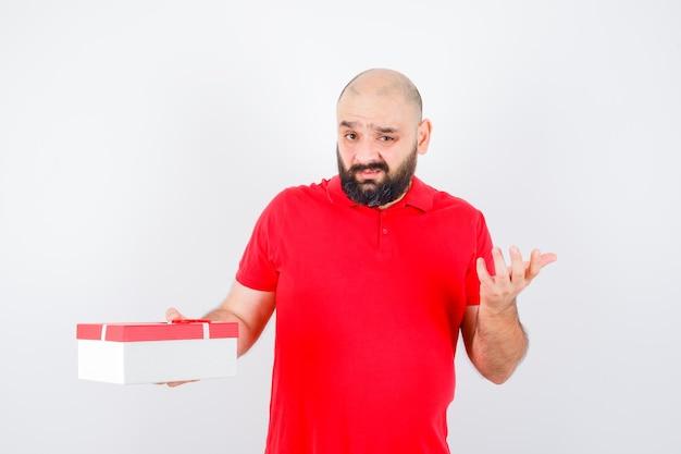 Jonge man in een rood t-shirt die de hand uitrekt in een vragend gebaar en er ontevreden uitziet, vooraanzicht.