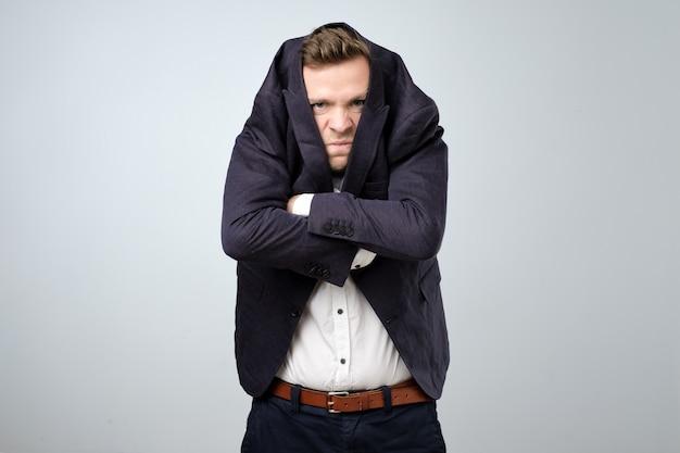 Jonge man in een te groot pak. hij is beledigd en ziet er gestrest uit