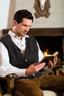 Jonge man in een traditionele berghut met open haard die de bijbel leest