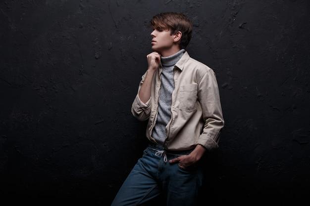 Jonge man in een trendy voorjaar jas in een vintage grijze trui met een modieus kapsel en spijkerbroek poseren in een donkere kamer in de buurt van de zwarte muur. stijlvolle aantrekkelijke kerel. kleding in amerikaanse stijl