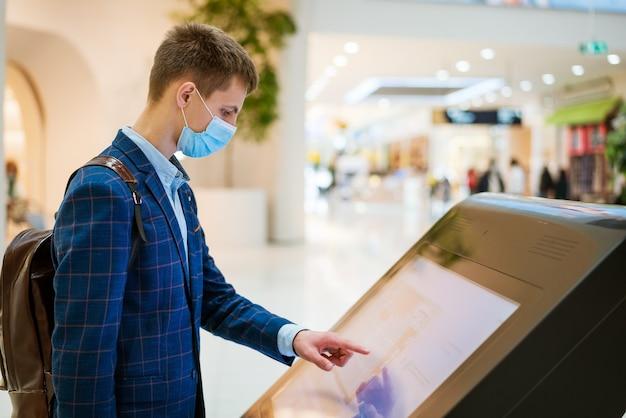 Jonge man in een winkelcentrum kijkt naar de monitor in een masker, het concept van zoeken op internet