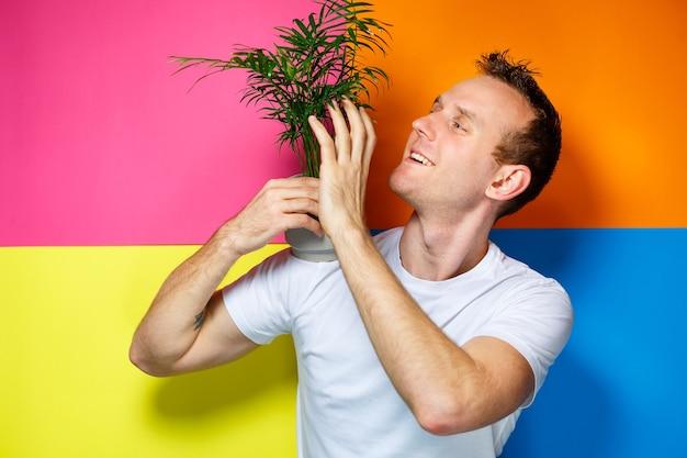 Jonge man in een wit t-shirt, kleurrijke achtergrond, decoratieve palm, emoties foto, huisplant, liefde voor de natuur