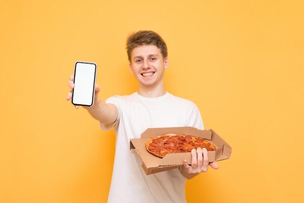 Jonge man in een wit t-shirt met een doos pizza in zijn handen, staande op een geel, toont een smartphone met een wit scherm in de camera en glimlacht