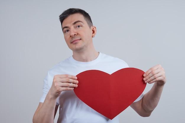 Jonge man in een wit t-shirt, met een hart van papier in zijn hand