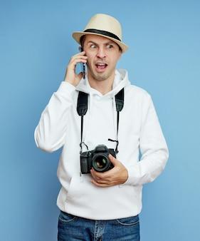 Jonge man in een witte trui met een hoed en een camera