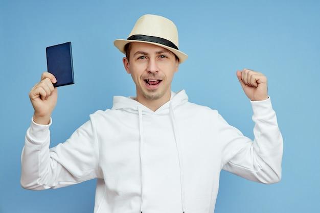 Jonge man in een witte trui met een hoed en paspoort