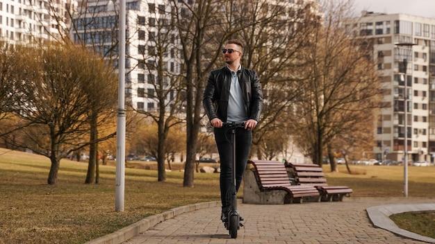 Jonge man in een zwarte jas en zonnebril rijdt op een elektronische scooter