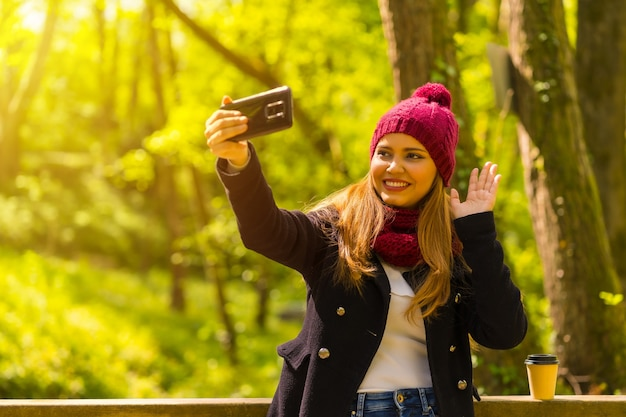 Jonge man in een zwarte jas, sjaal en rode wollen muts genietend in een herfstpark, zwaaiend op een videogesprek met de telefoon