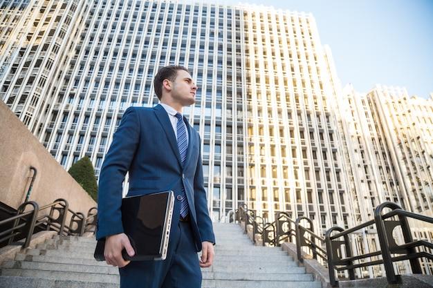 Jonge man in elegante pak poseren met de laptop in zijn hand wegkijken.