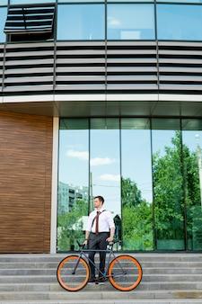 Jonge man in formalwear opzij kijken terwijl hij op de trap staat met de buitenkant van het moderne zakencentrum