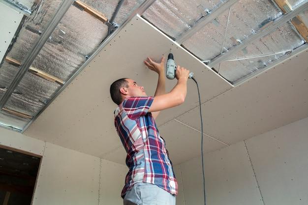Jonge man in gebruikelijke kleding en werkhandschoenen tot vaststelling van gipsplaten verlaagd plafond aan metalen frame met behulp van elektrische schroevendraaier op plafond geïsoleerd met glanzende aluminiumfolie. diy, doe het zelf concept.