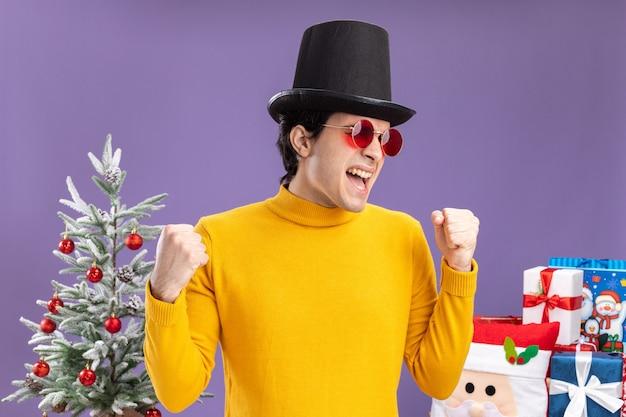 Jonge man in gele coltrui en bril met zwarte hoed blij en opgewonden gebalde vuisten staan naast een kerstboom en presenteert over paarse muur
