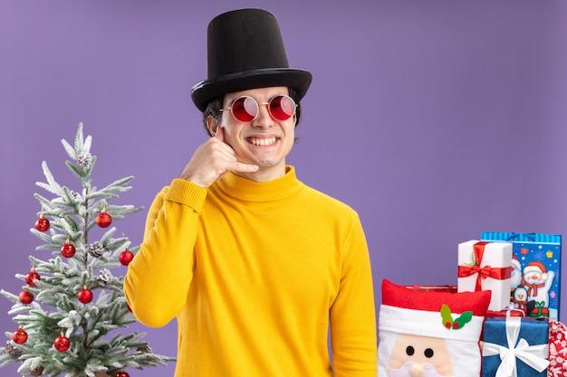 Jonge man in gele coltrui en bril met zwarte hoed camera kijken met glimlach op gezicht maken bel me gebaar staande naast een kerstboom en cadeautjes op paarse achtergrond